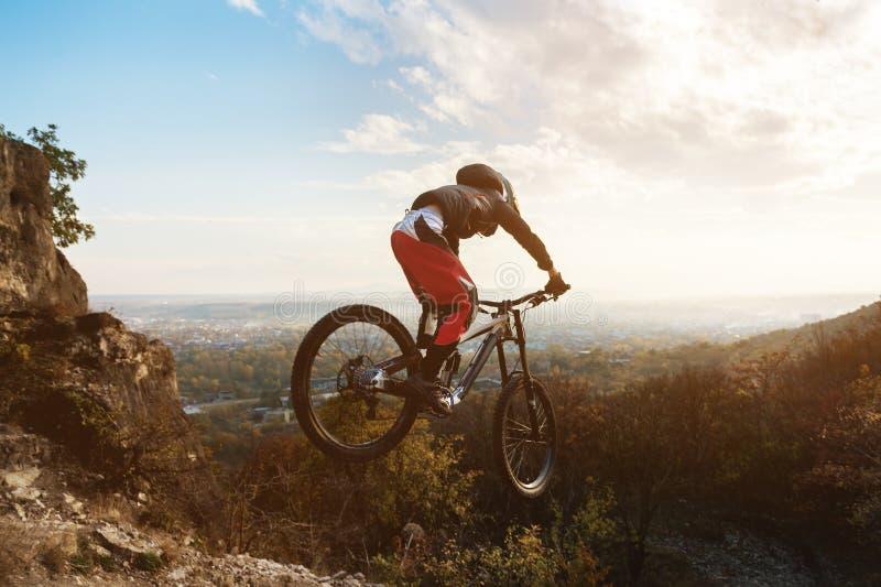 Un giovane cavaliere alla ruota del suo mountain bike fa un trucco nel salto sul trampolino della montagna in discesa fotografia stock