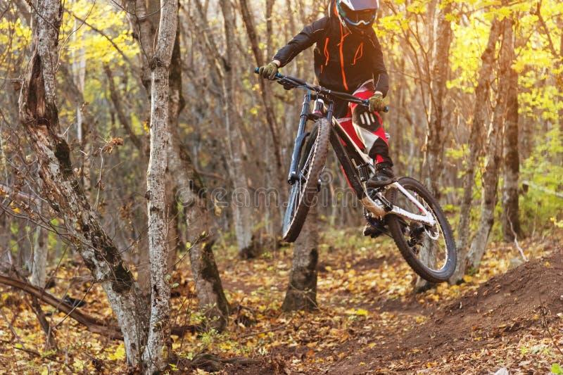 Un giovane cavaliere alla ruota del suo mountain bike fa un trucco nel salto sul trampolino della montagna in discesa immagini stock