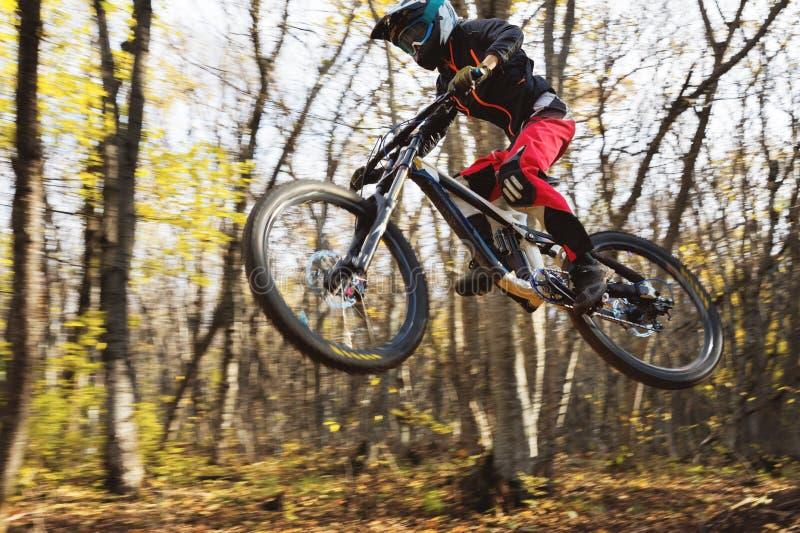 Un giovane cavaliere alla ruota del suo mountain bike fa un trucco nel salto sul trampolino della montagna in discesa fotografia stock libera da diritti