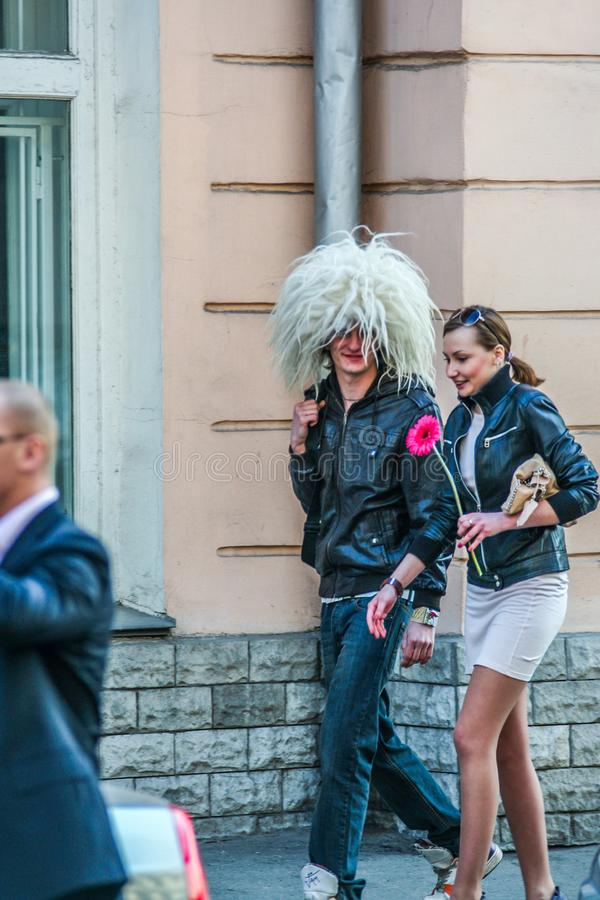 Un giovane che indossa cappello di lana e ragazza divertenti che camminano giù la via fotografia stock