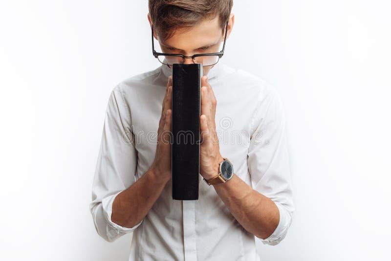 Un giovane che prega a Dio o a Jesus Christ, piegato, su un fondo bianco, chiedente l'aiuto fotografia stock