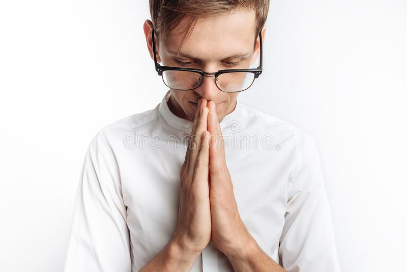 Un giovane che prega a Dio o a Jesus Christ, piegato, su un fondo bianco, chiedente l'aiuto immagine stock