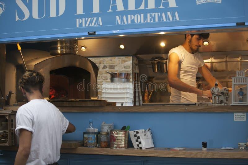 Un giovane che produce una pizza in un caffè mobile immagine stock libera da diritti
