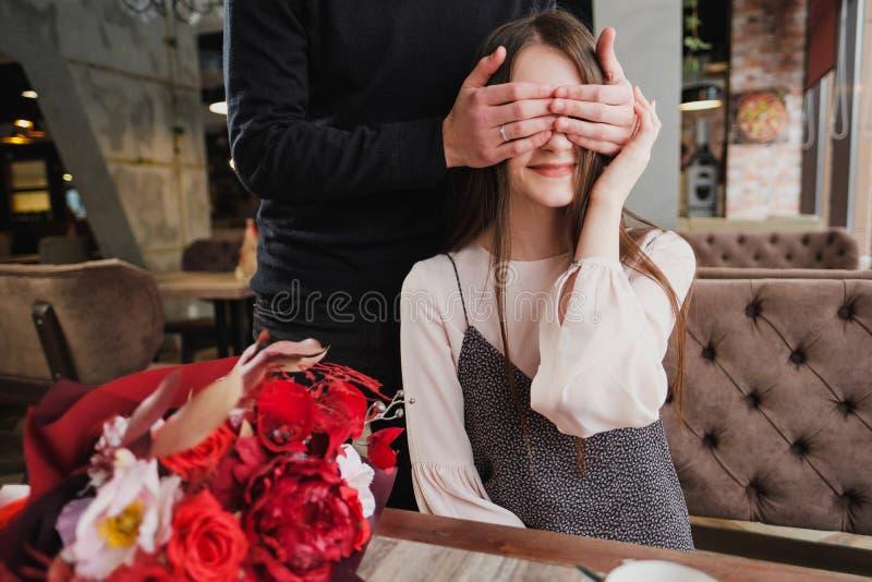 Un giovane chiude i suoi occhi alla ragazza, la sua moglie e dà un mazzo dei fiori rossi in un caffè dalla finestra immagine stock libera da diritti