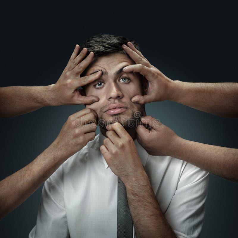 Un giovane circondato a mano come i suoi propri pensieri fotografia stock libera da diritti