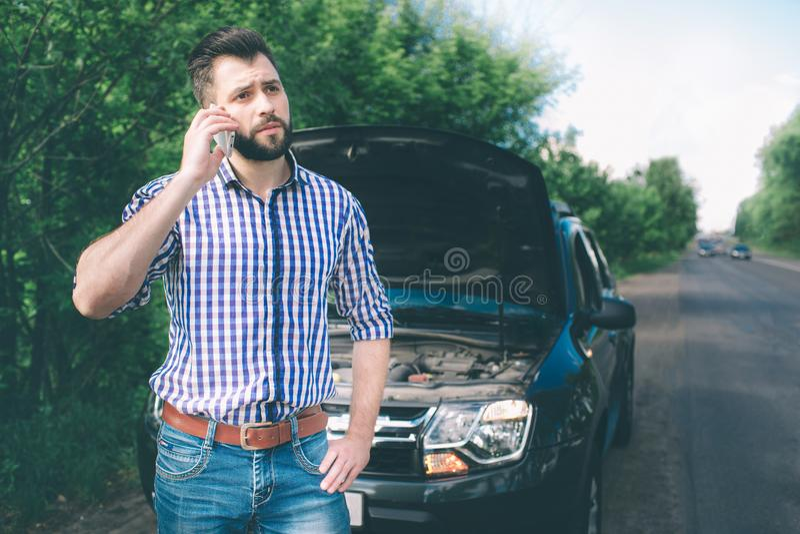 Un giovane con un'automobile nera che ha ripartito sulla strada Sta richiedendo il tecnico per arrivare fotografia stock libera da diritti