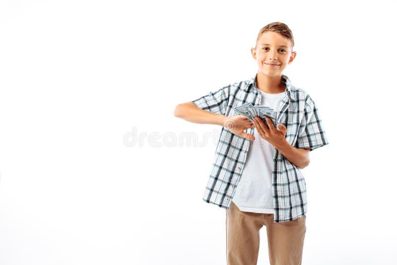 Un giovane con i vetri getta cento fatture dei dollari, un ritratto di riuscito adolescente in una camicia nello studio su una b  fotografia stock