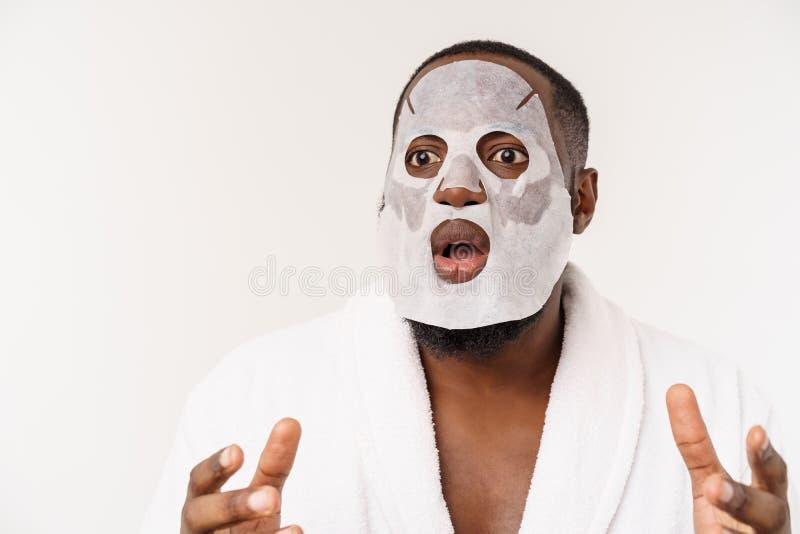 Un giovane con la maschera di carta sul fronte che sembra colpito con una bocca aperta, isolata su un fondo bianco immagini stock