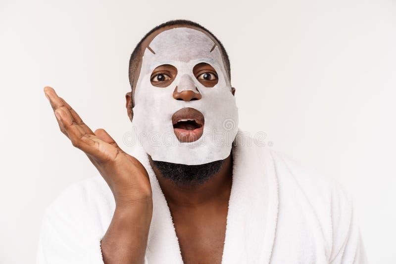 Un giovane con la maschera di carta sul fronte che sembra colpito con una bocca aperta, isolata su un fondo bianco fotografia stock