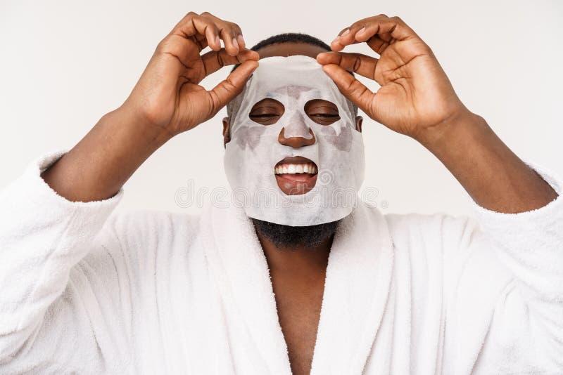 Un giovane con la maschera di carta sul fronte che sembra colpito con una bocca aperta, isolata su un fondo bianco fotografie stock