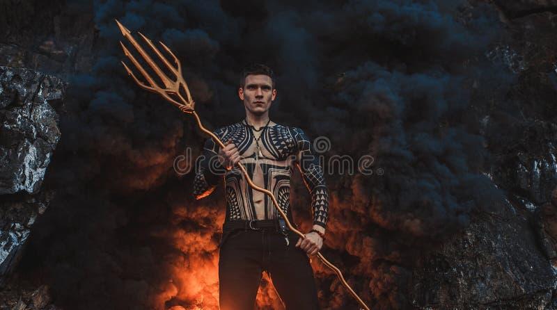 Un giovane con un tridente contro lo sfondo di fuoco e di fumo fotografie stock libere da diritti