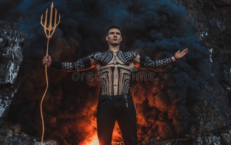 Un giovane con un tridente contro lo sfondo di fuoco e di fumo immagine stock