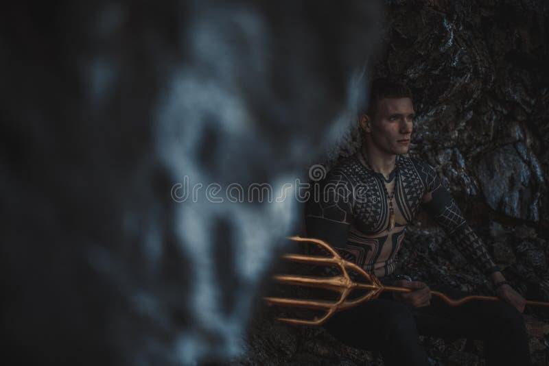 Un giovane con un tridente in sue mani contro lo sfondo delle rocce immagini stock
