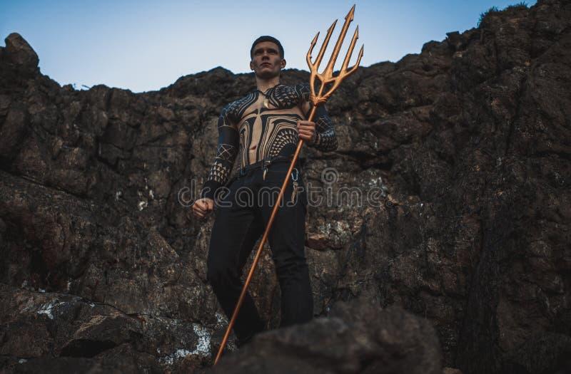 Un giovane con un tridente in sue mani contro lo sfondo delle rocce immagini stock libere da diritti