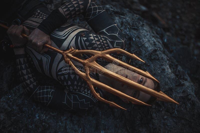 Un giovane con un tridente in sue mani si trova sulla roccia immagini stock