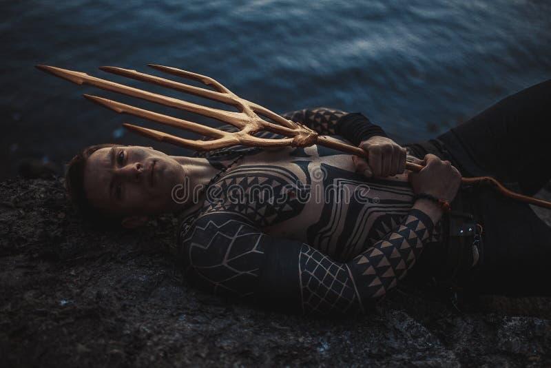 Un giovane con un tridente in sue mani si trova sulla roccia vicino all'acqua fotografie stock libere da diritti