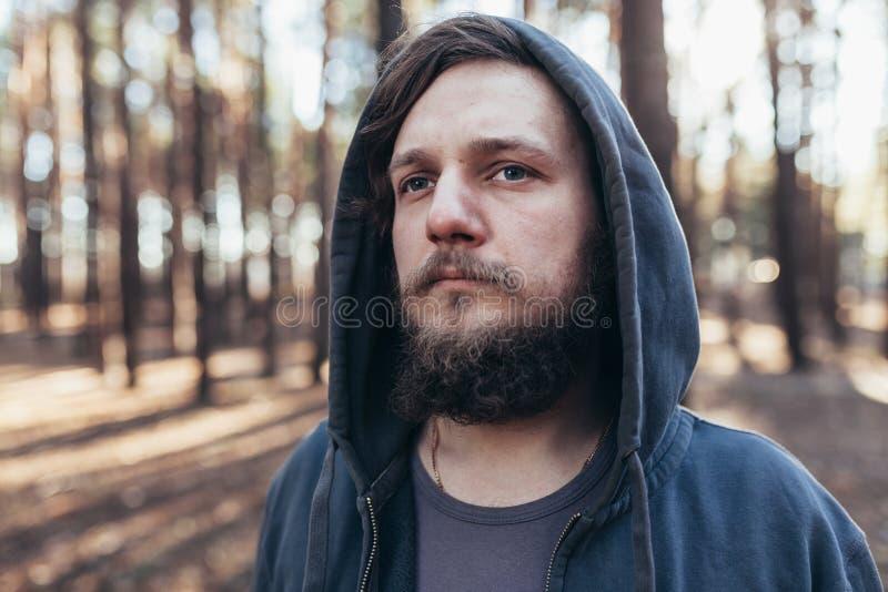 Un giovane con una barba cammina in un ritratto dell'abetaia di un uomo barbuto brutale in un cappuccio fotografia stock