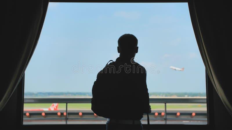 Un giovane con uno zaino sul suo indietro guarda l'aeroplano decollare dalla finestra della sua camera di albergo e va ulteriore fotografia stock