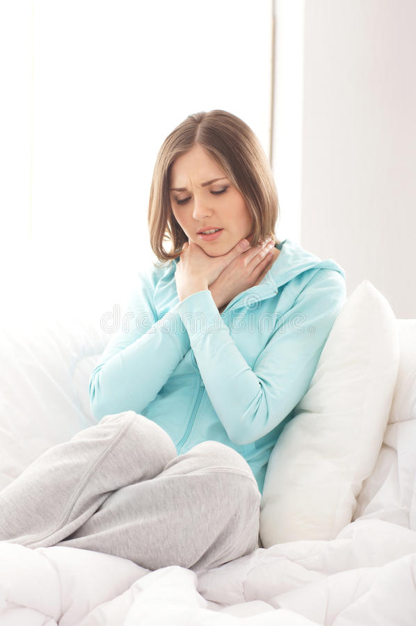 Un giovane dolore castana di sensibilità della donna in sua gola immagini stock