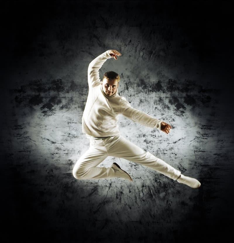Un giovane ed uomo sportivo che fa una posa di danza moderna fotografia stock