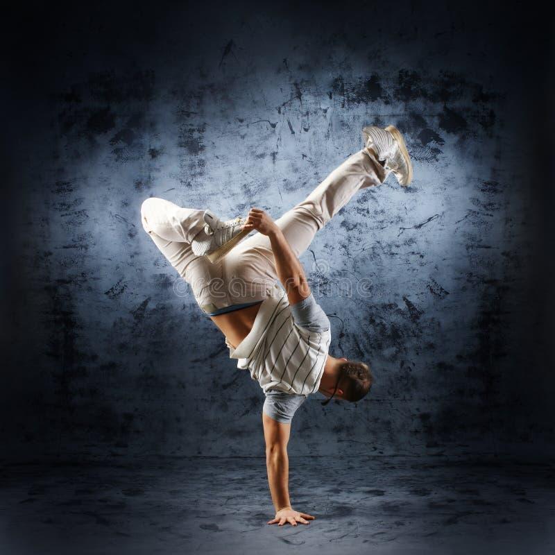Un giovane ed uomo sportivo che fa una posa di danza moderna fotografie stock libere da diritti