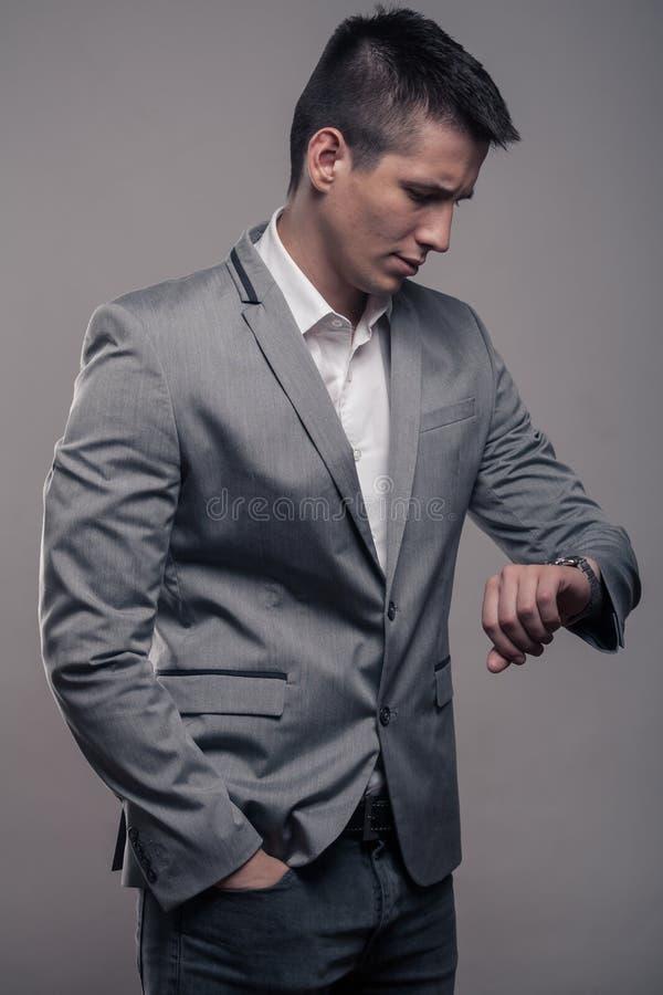 Un giovane, ente superiore, vestiti convenzionali, guardanti per guardare immagine stock