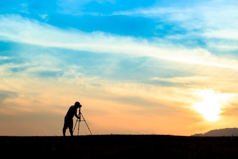 Un giovane fotografo durante il tramonto fotografia stock libera da diritti