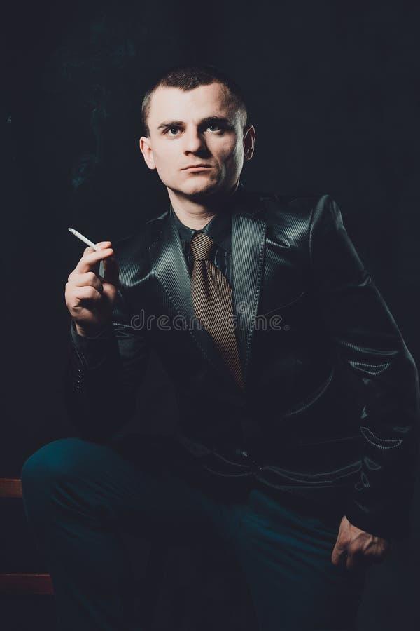 Un giovane fuma una sigaretta, un fondo nero, un vestito nero classico fotografia stock