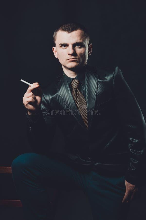 Un giovane fuma una sigaretta, un fondo nero, un vestito nero classico fotografia stock libera da diritti