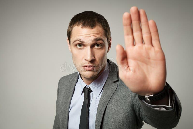 Un giovane gesto di arresto di rappresentazione dell'uomo d'affari immagini stock
