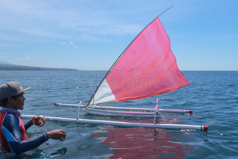 Un giovane indonesiano sta nel mare e prepara una nave di modello per la concorrenza Piccola barca a vela di legno con la vela bi fotografia stock libera da diritti