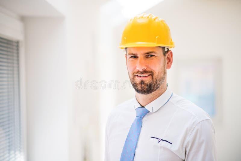 Un giovane ingegnere o architetto con la camicia, il legame ed il casco bianchi in una stanza immagine stock