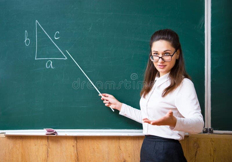 Un giovane insegnante spiega il per la matematica vicino al bordo fotografia stock libera da diritti