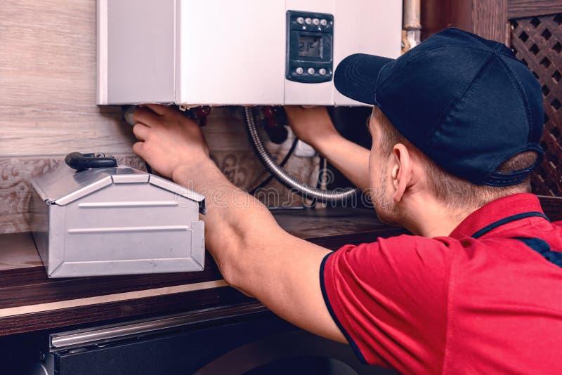 Un giovane lavoratore qualificato regola la caldaia a gas prima dell'uso immagine stock