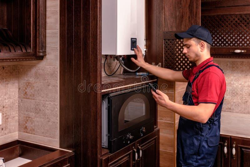 Un giovane lavoratore qualificato regola la caldaia a gas prima dell'uso fotografia stock libera da diritti