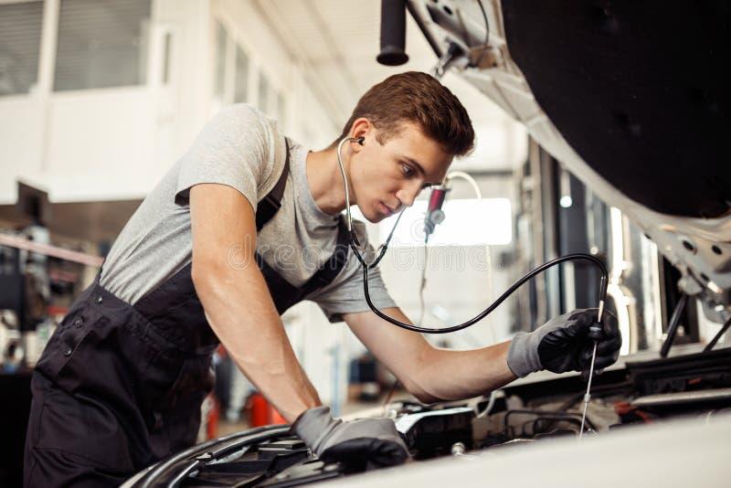 Un giovane ma meccanico qualificato sta conducendo un esame dettagliato di un'automobile fotografia stock libera da diritti