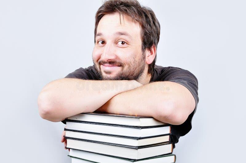 Un giovane maschio piacevole sta sorridendo sui libri fotografia stock