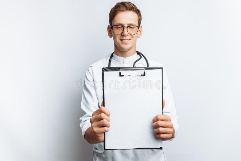 Un giovane medico mostra una cartella con un foglio bianco sulla macchina fotografica, su un fondo bianco, per la pubblicità e l' immagine stock