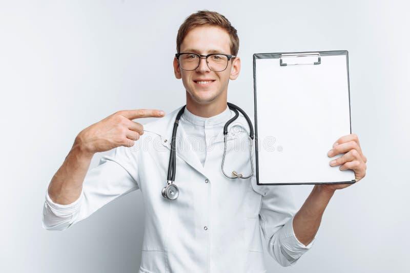 Un giovane medico mostra una cartella con un foglio bianco sulla macchina fotografica, su un fondo bianco, per la pubblicità e l' fotografia stock libera da diritti