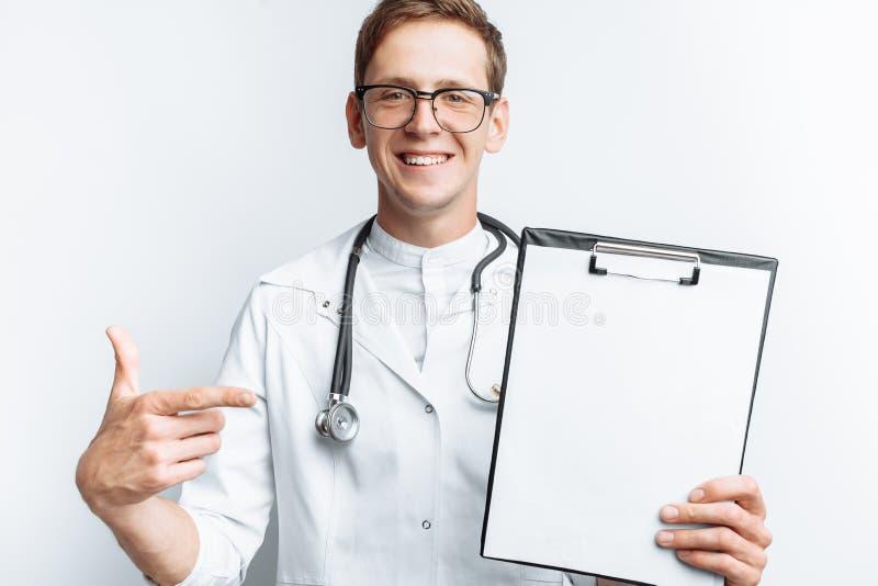 Un giovane medico mostra una cartella con un foglio bianco sulla macchina fotografica, su un fondo bianco, per la pubblicità e l' fotografia stock