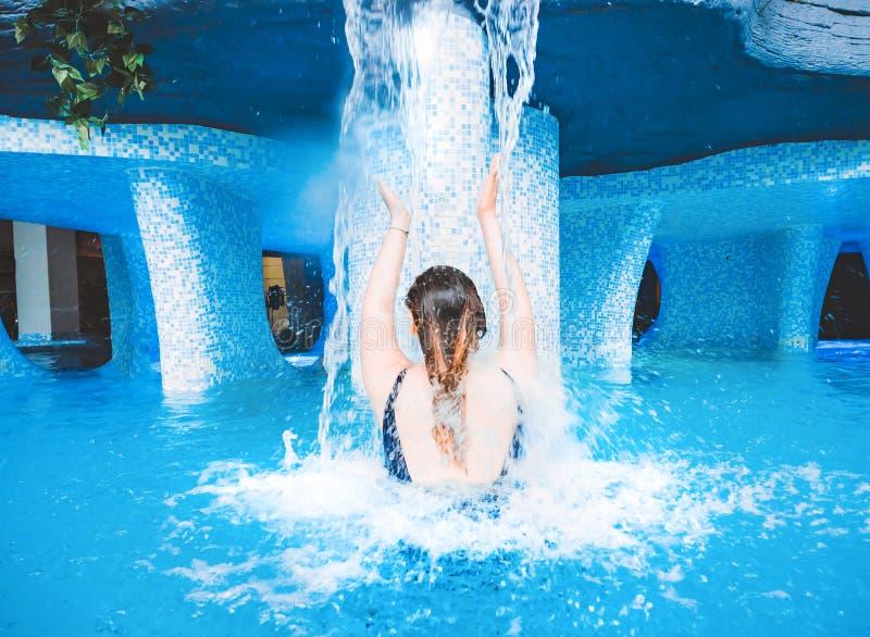 Un giovane nuoto sorridente della ragazza nello stagno con chiara acqua blu Una ragazza sta stando indietro sotto una corrente di immagini stock