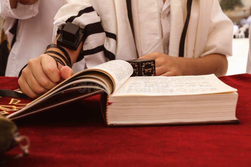 Un giovane pregante passa con un tefillin che tiene un libro della bibbia, mentre legge un pregare ad un rituale ebreo immagini stock