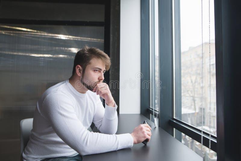 Un giovane premuroso si siede all'ufficio alla tavola e guarda nella finestra Un uomo pensa nell'ufficio alla tavola fotografia stock libera da diritti