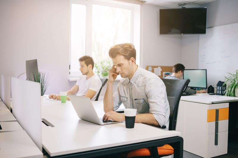 Un giovane programmatore sta esaminando il computer Il grafico sta ritenendo ai progetti futuri Il giovane tipo fotografia stock libera da diritti