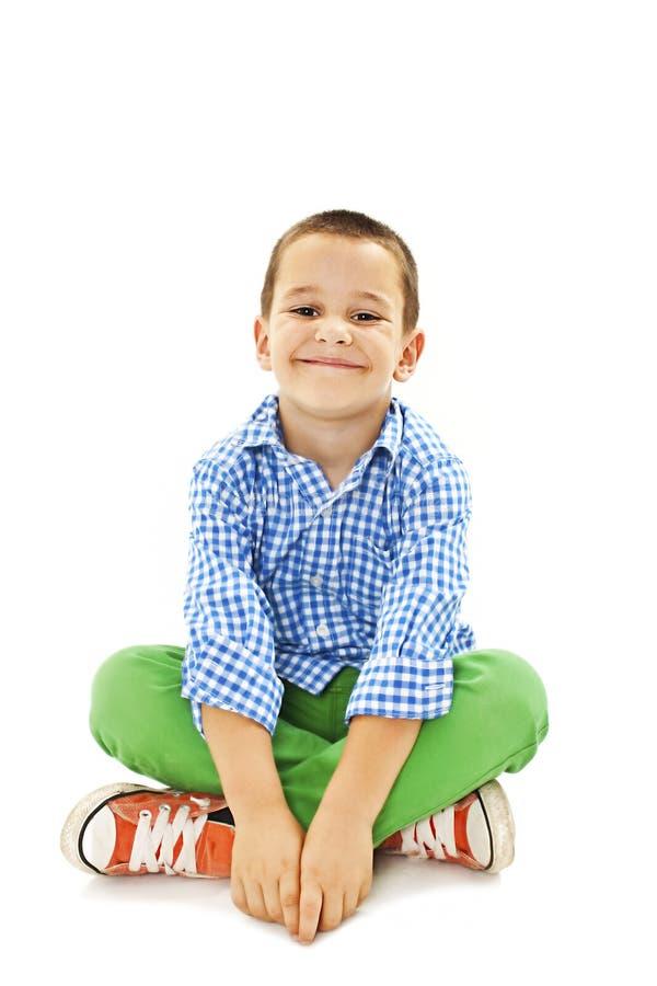 Un giovane ragazzo allegro che si siede sul pavimento immagine stock