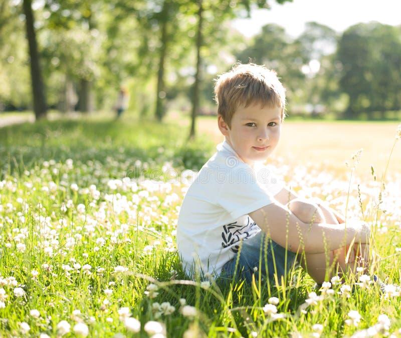 Un giovane ragazzo caucasico che si siede in un prato dell'estate si è acceso da lig posteriore fotografia stock
