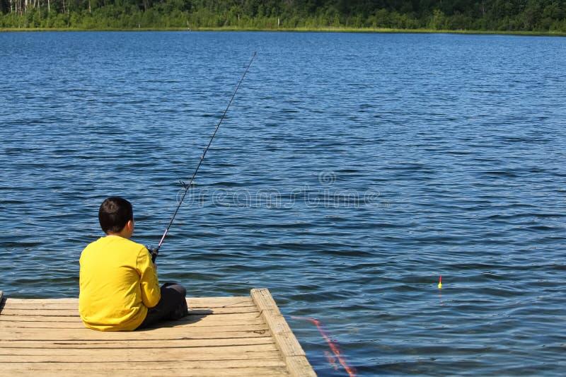 Un giovane ragazzo che si siede su un bacino e su una pesca fotografie stock libere da diritti