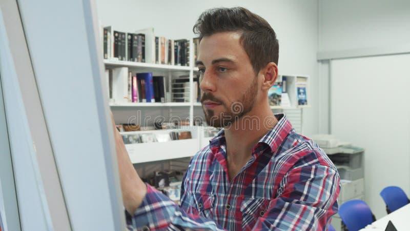 Un giovane scrive su una lavagna e sui erases immagine stock libera da diritti