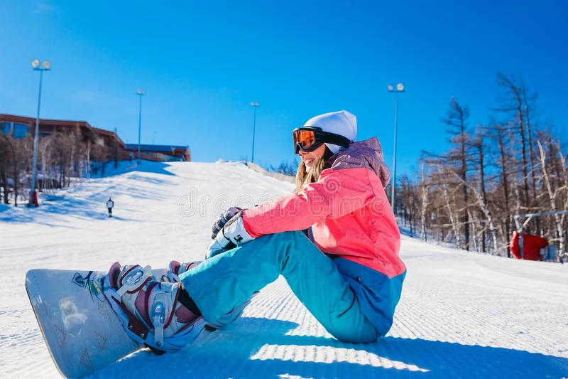 Un giovane snowboarder si siede su un pendio di montagna fotografia stock libera da diritti