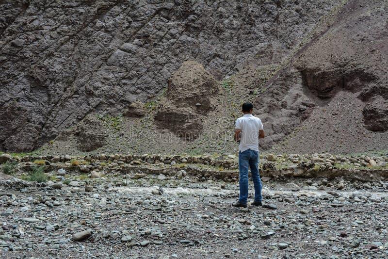 Un giovane sta sulla montagna fotografia stock